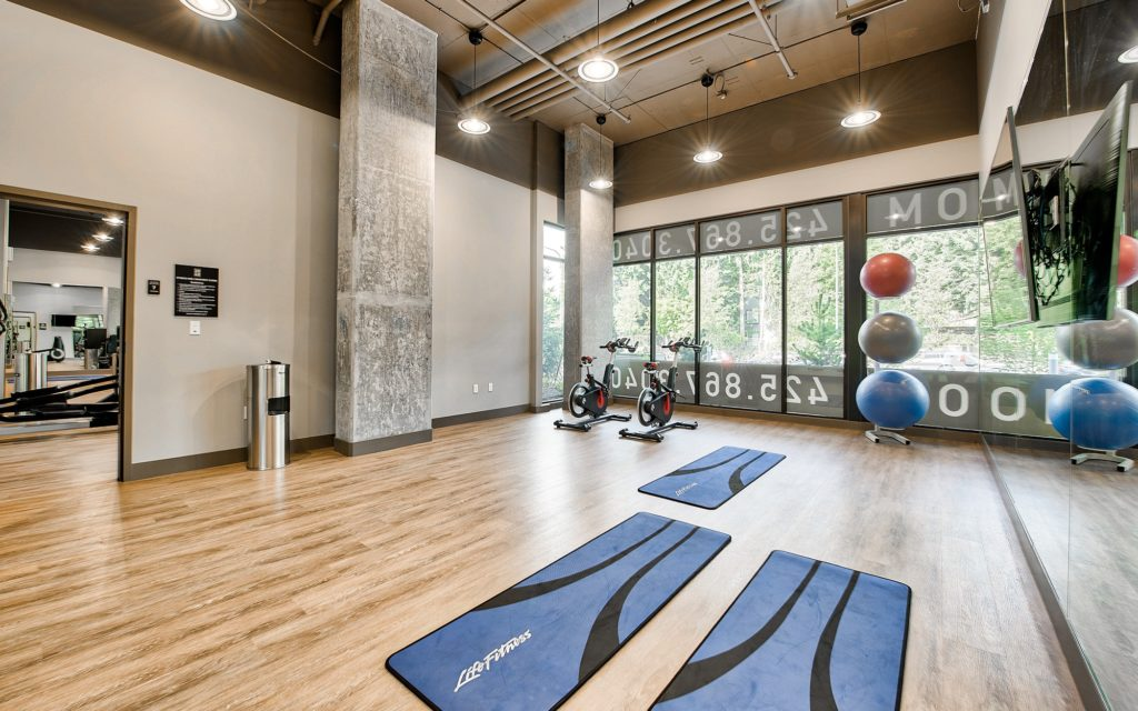 Fitness and yoga studio with wood flooring, mirrored wall with wall mounted TV, exposed pipe ceiling, stationary bikes, and yoga mats and balls.