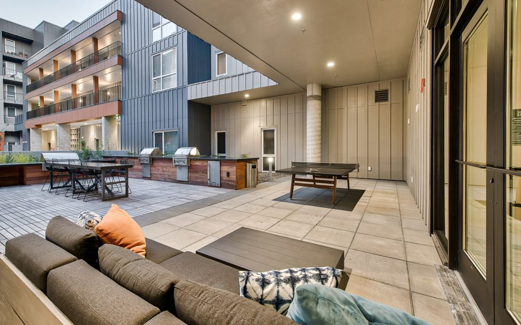 Outdoor courtyard with pink pong table, three built-in grilling stations, high-top dining table with bar stools, and lounge seating.