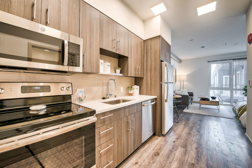 Alternate view of One-wall style kitchen with wood flooring, light countertops, and stainless-steel appliances including a top freezer style refrigerator, dishwasher, single basin undercounted sink, microwave, and over and stove combo.