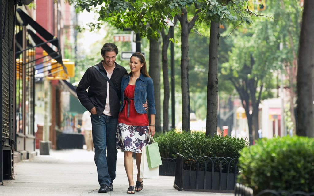 Couple walking down a city sidewalk with shopping bags