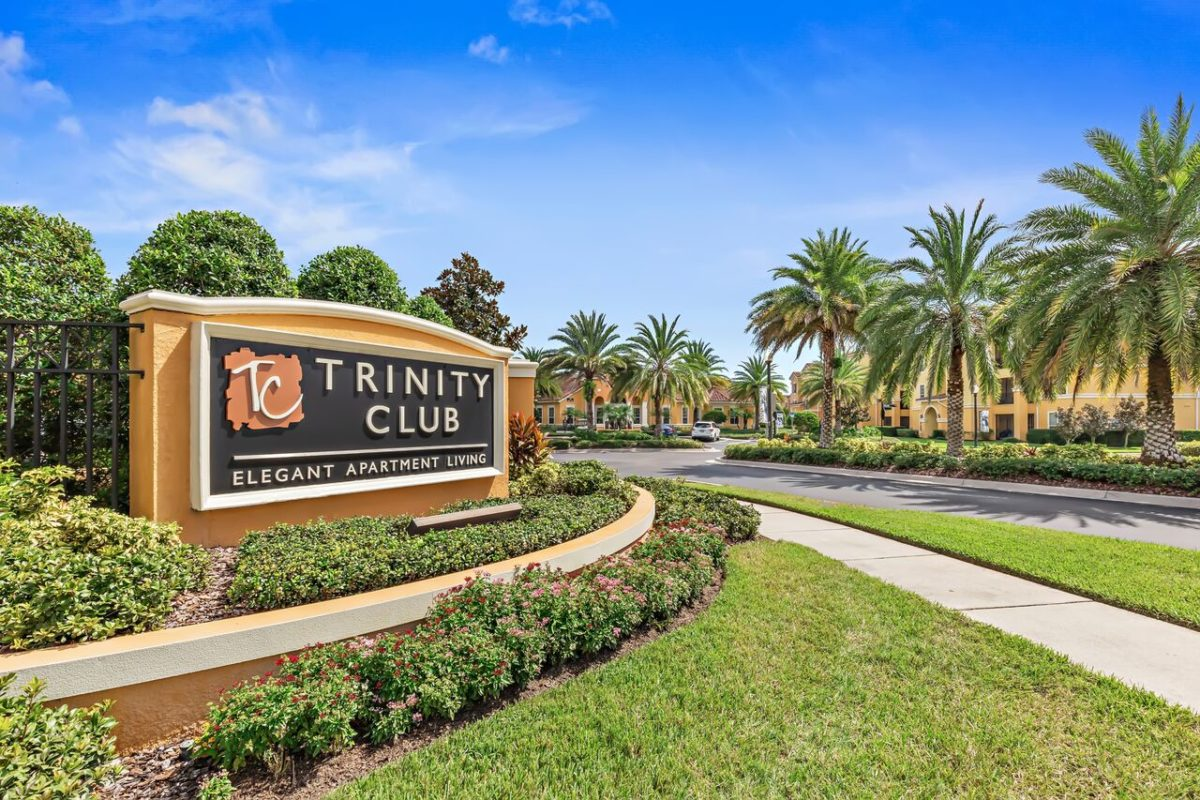 Trinity Club Monument Sign in front of driveway with palm trees