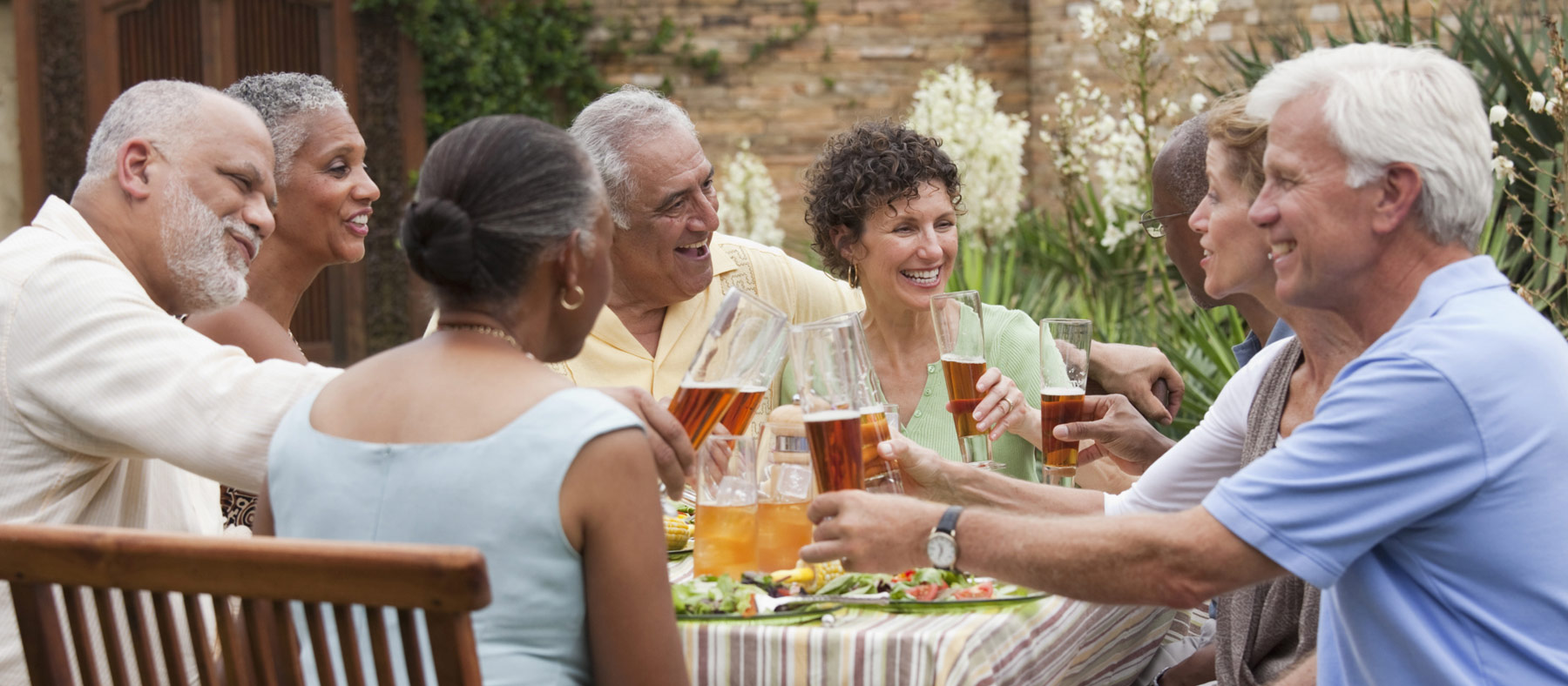 Group of happy senior friends seated around outdoor table toasting drinks
