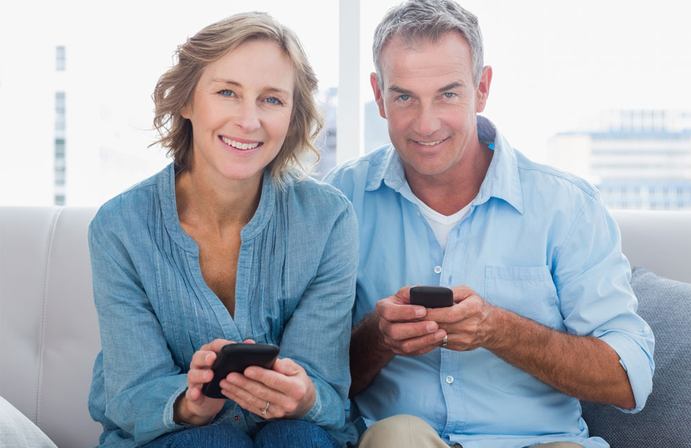 Happy senior couple using smartphones