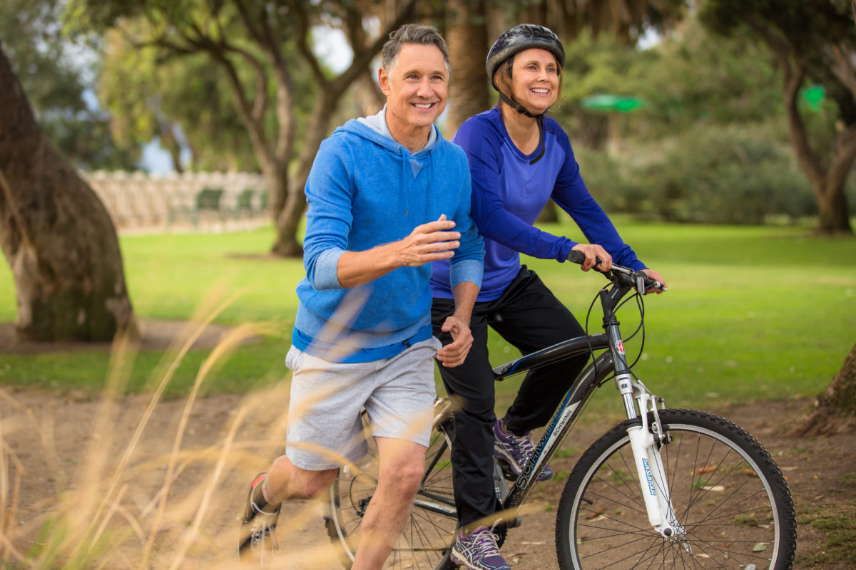 Happy senior couple jogging and riding bicycle outdoors