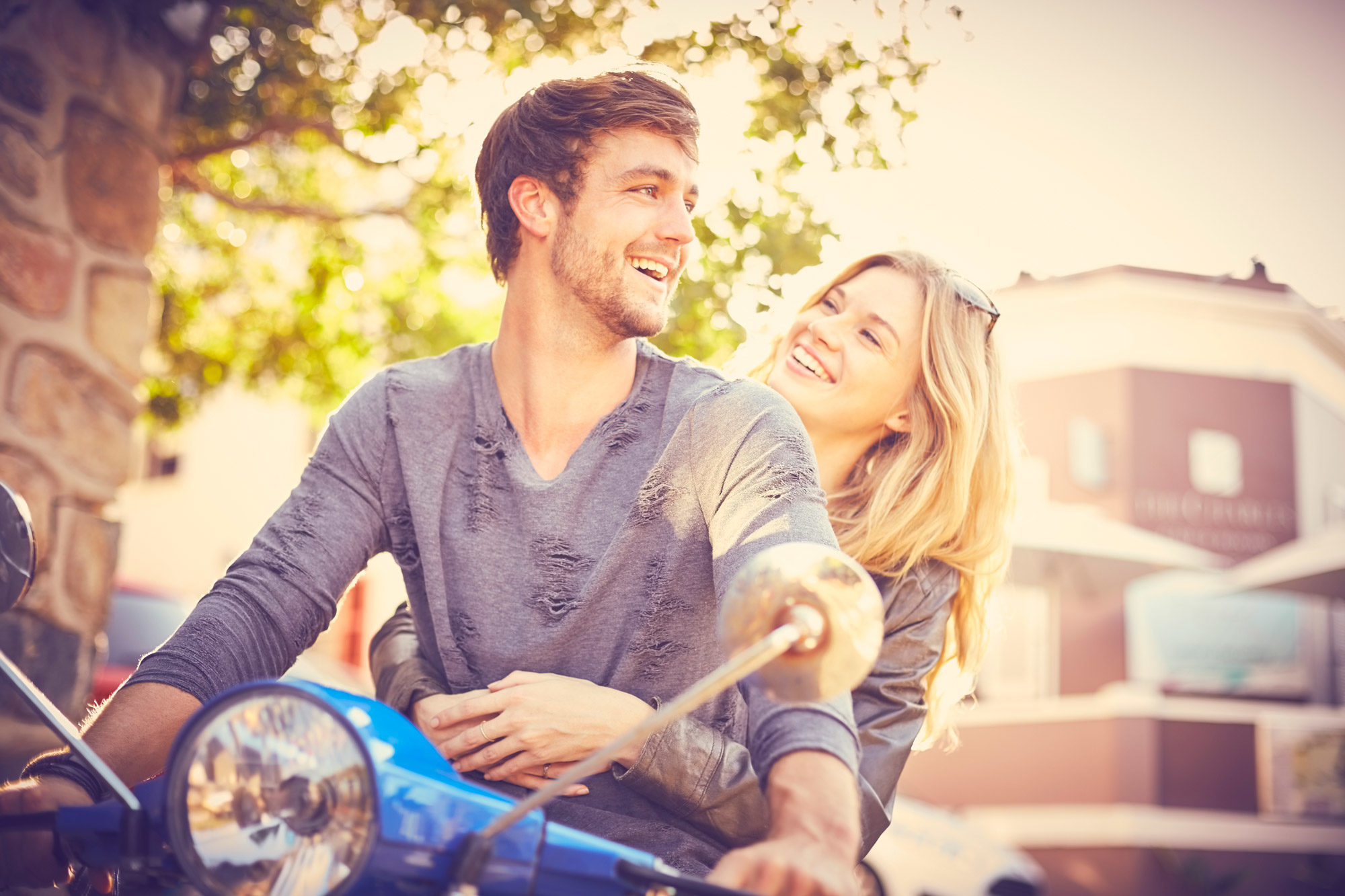 Man and woman smiling on moped