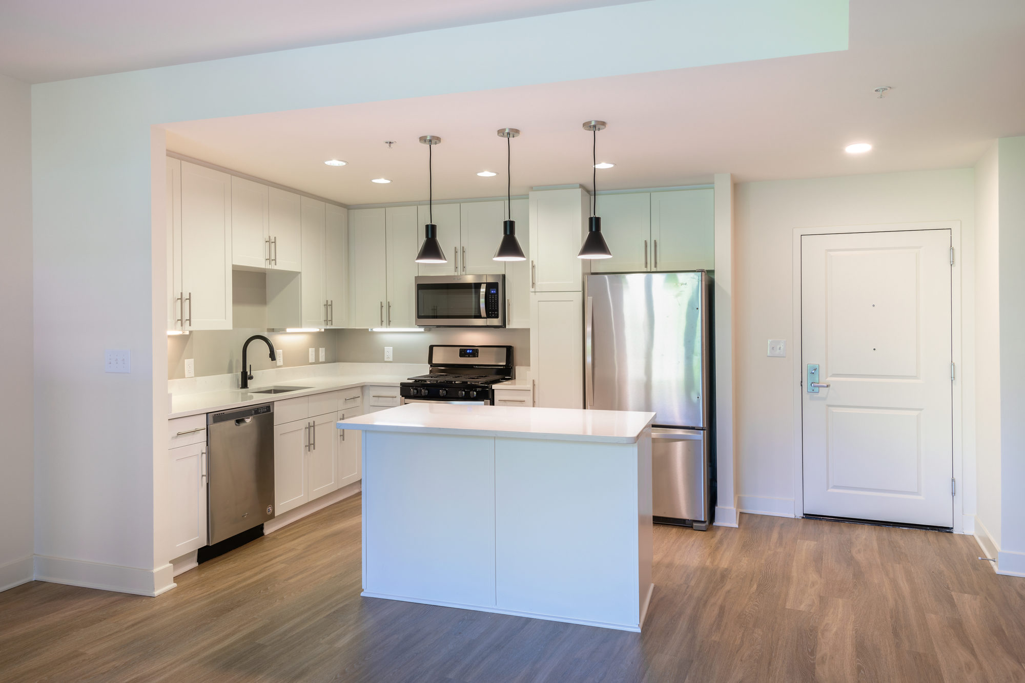 white kitchen shot with island, white cabinets and countertops, stainless steel appliances, black pendant lighting and single basin sink