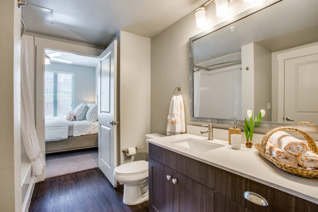 Interior of model apartment bathroom with framed mirrors, wood cabinets, and hardwood floors