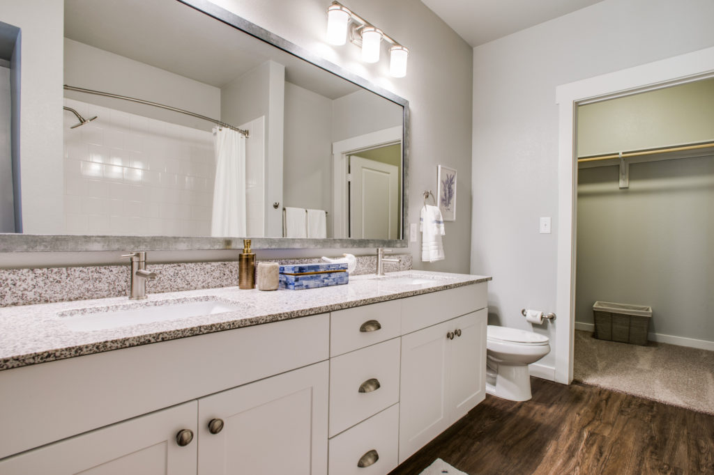 Model apartment bathroom with double vanity, large framed mirror, hardwood floors, and walk-in closet