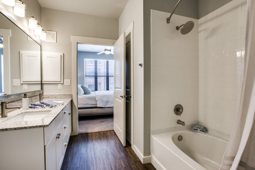 Model apartment bathrooms with double vanity, granite countertop, and tub-shower combination