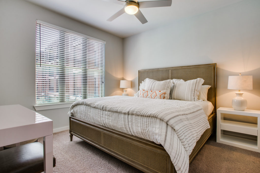Carpeted apartment bedroom with queen bed, ceiling fan, and window with wood blinds