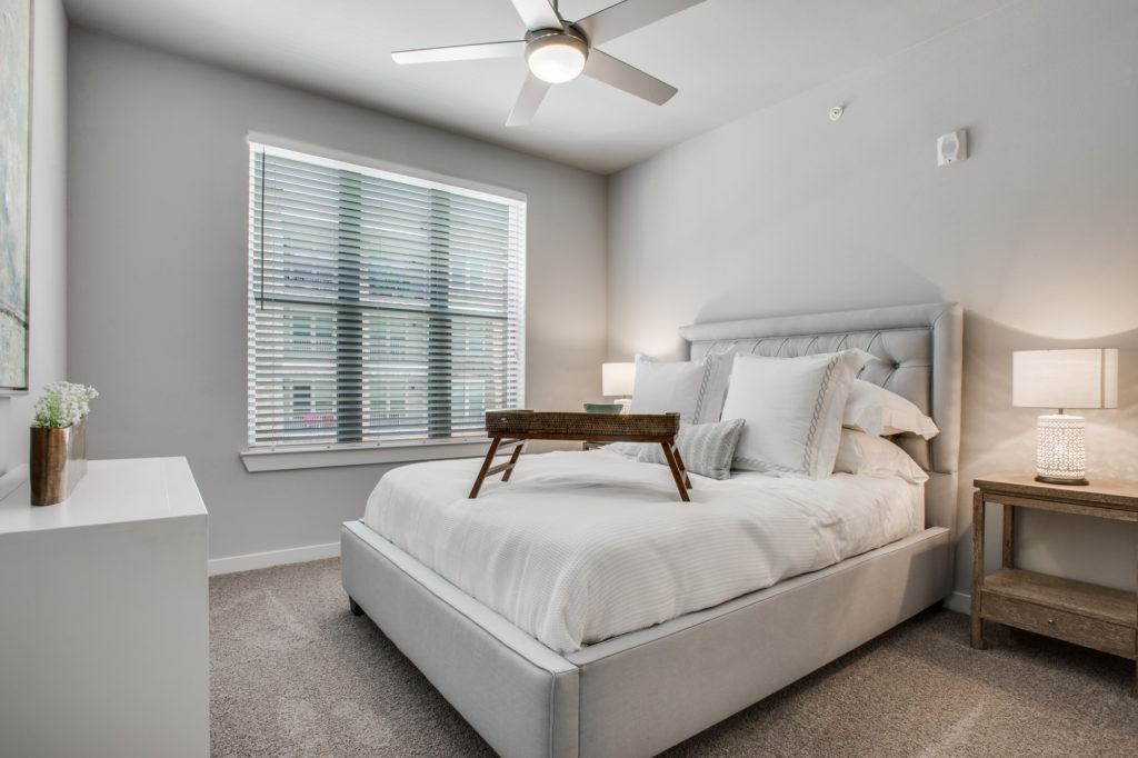 Model apartment bedroom with king bed, large window with wood blinds, and ceiling fan