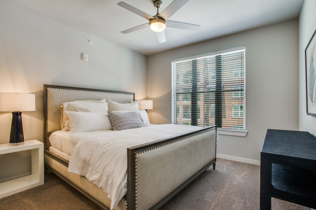 Model apartment bedroom with large bed, ceiling fan, and window with wood blinds
