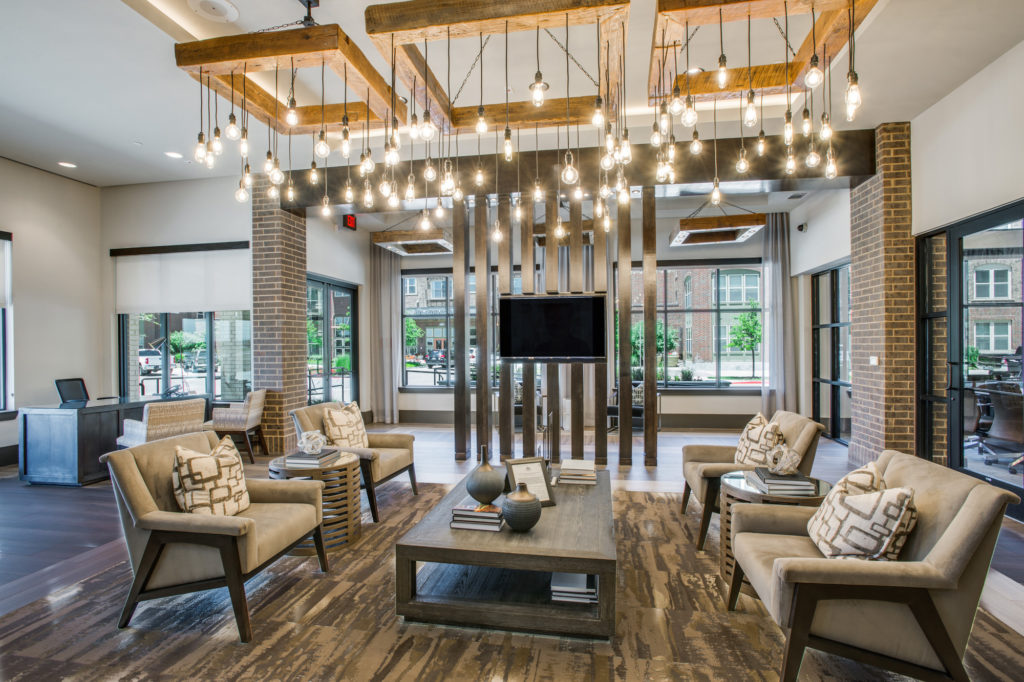 Community leasing lobby with designer lighting, plentiful seating, and television