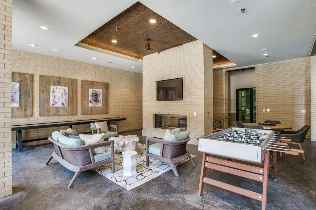 Community game room with foosball table, TV and fireplace, shuffleboard, and seating