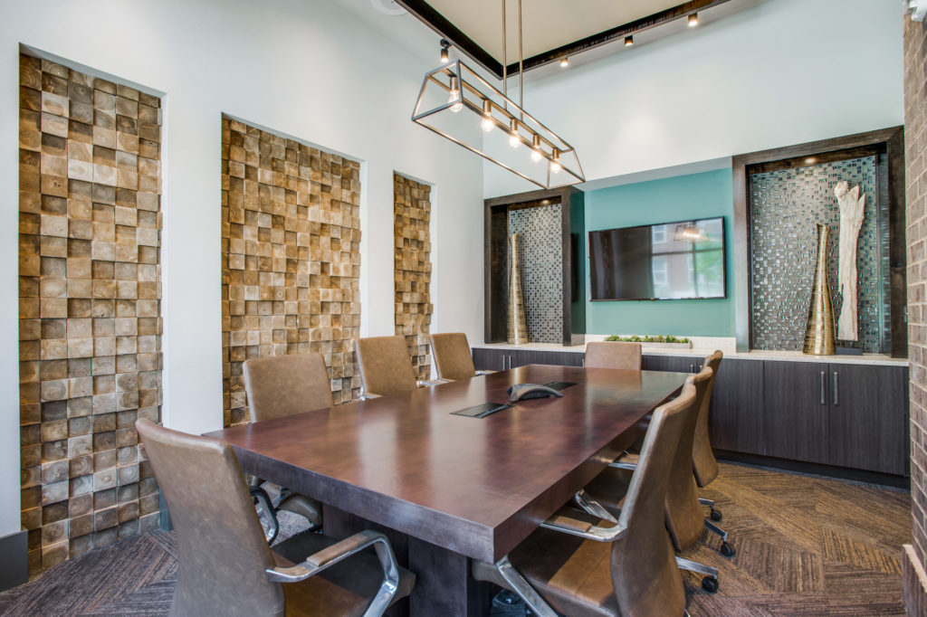 Community conference room with large meeting table, TV, and designer lighting