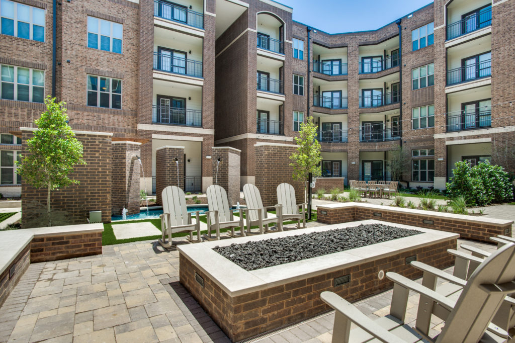 Community brick courtyard enclosure with fire pit, lawn chairs, and fountains