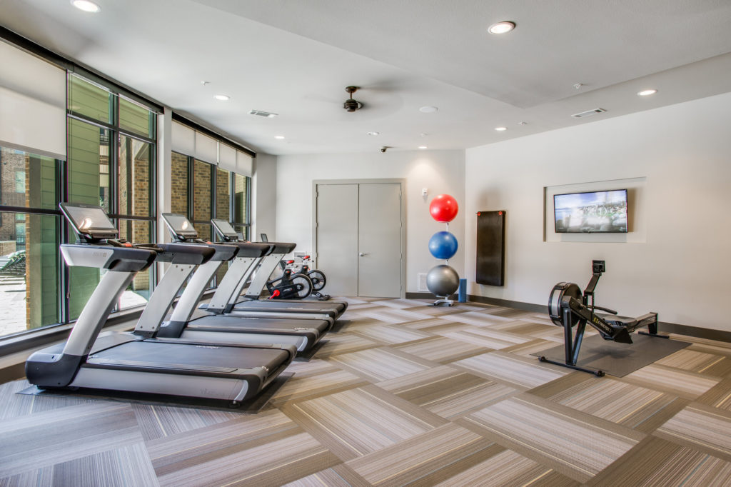 Fitness center with treadmills, cardio equipment, and strength training equipment