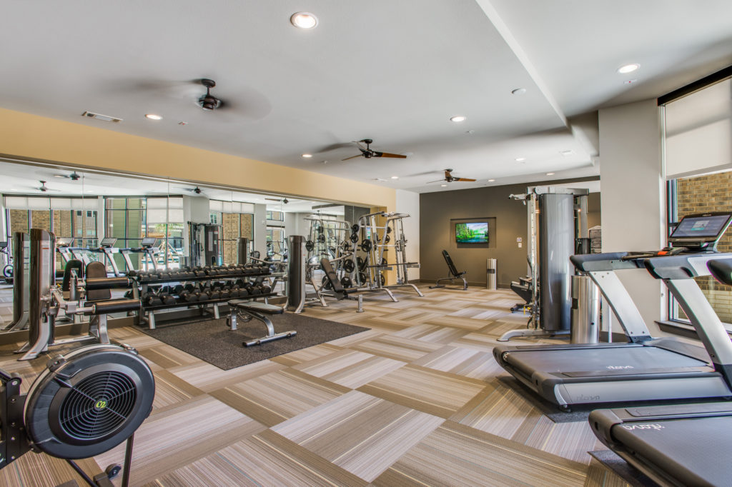 Fitness center with cardio machines, strength training equipment, and free weights