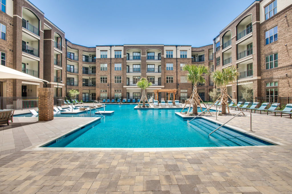 Large resort-style swimming pool with palm trees in central courtyard
