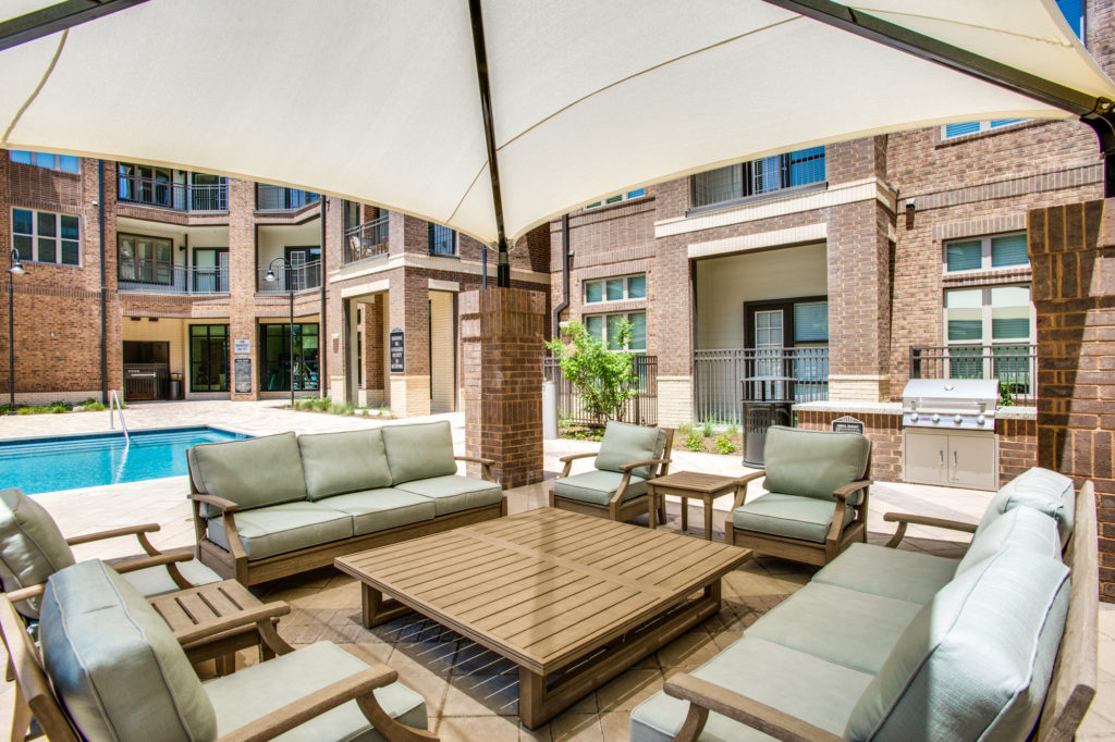Large poolside gazebo with comfortable couches and table