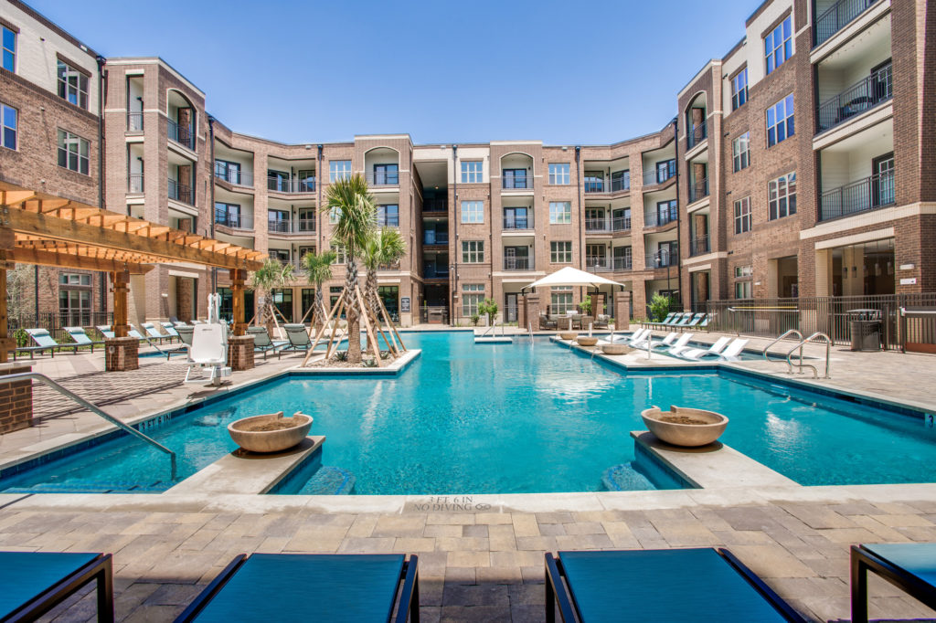 Community swimming pool and lounge areas with view of apartment buildings