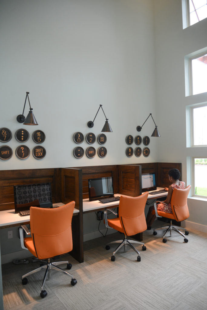 Business center with three computers, desks with privacy walls, and office chairs