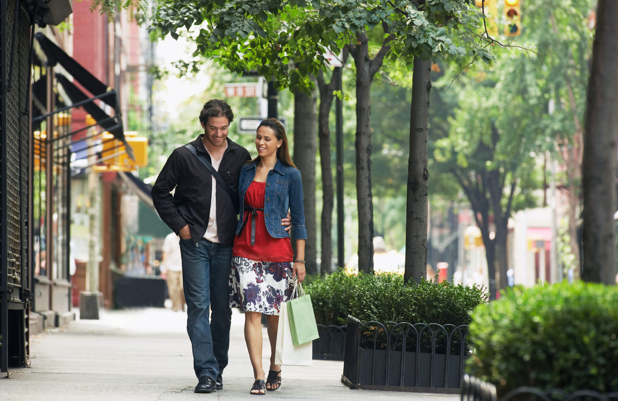 Couple walking outdoors on city sidewalk holding shopping bags