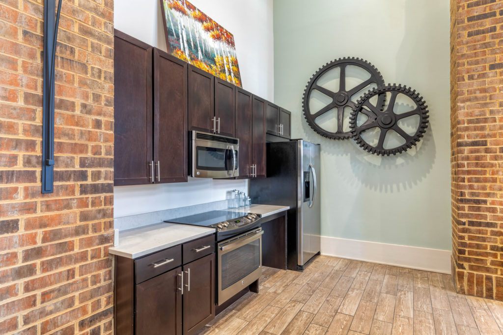 Clubhouse kitchen area with stainless steel microwave, range and refrigerator, marble countertops and cogwheel sculpture on the wall.
