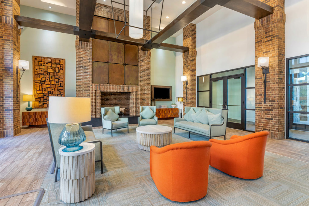 Clubhouse with comfortable chairs and couches, brick pillars with sconces and community fireplace with wall mounted wooded sculpture accent art.