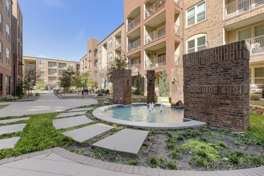 Outdoor fountain water feature with 3 water spouts, walkable paving and lush landscaping with apartment balconies in the background.