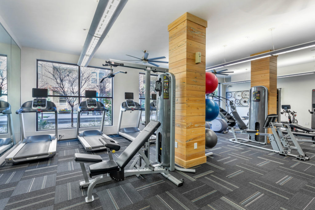 Fitness center interior with treadmills, weight benches, stair stepper, and medicine balls with large windows looking out towards the pool area.