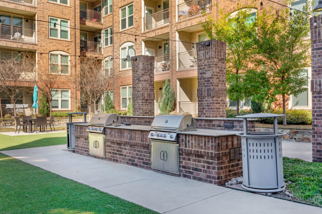 Set of outdoor stainless steel grills with countertop prep area and brick surrounds.