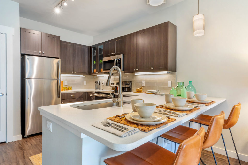 U-shaped kitchen with countertop bar seating 3 with place settings, large single basin sink with gooseneck faucet, dark wood upper and lower cabinetry and stainless steel appliances.