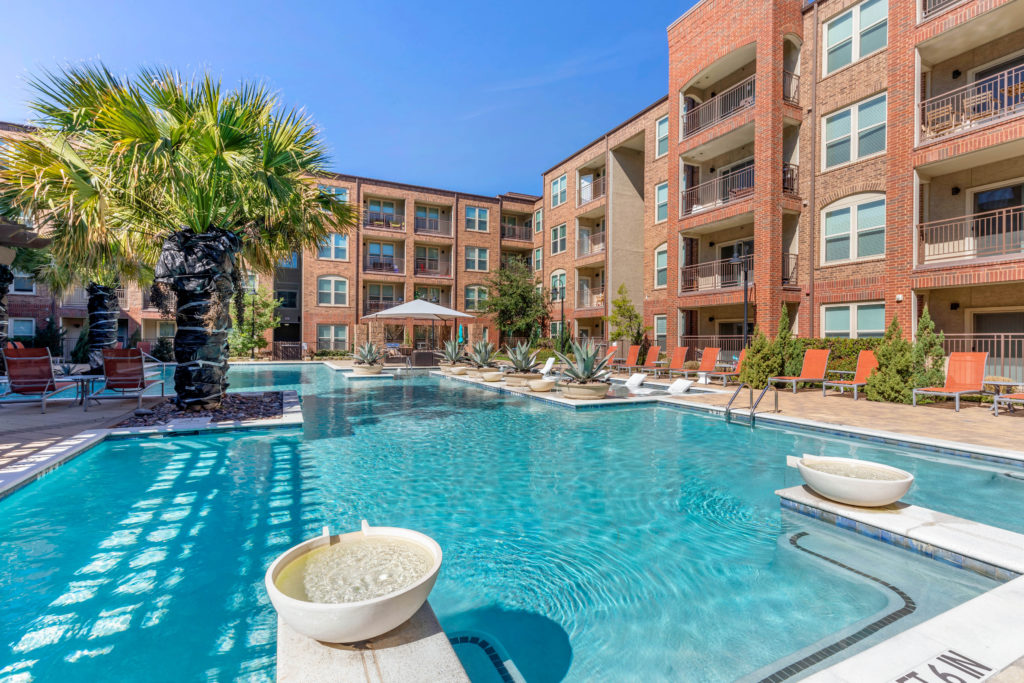 Wide view of swimming pool with water features, palm trees, shaded cabana, lounge seating and apartment balconies in the background.