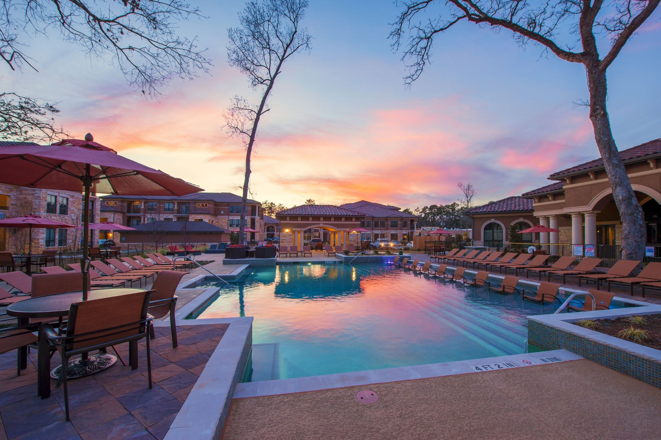 Sunset view of pool with landscaping and patio seating