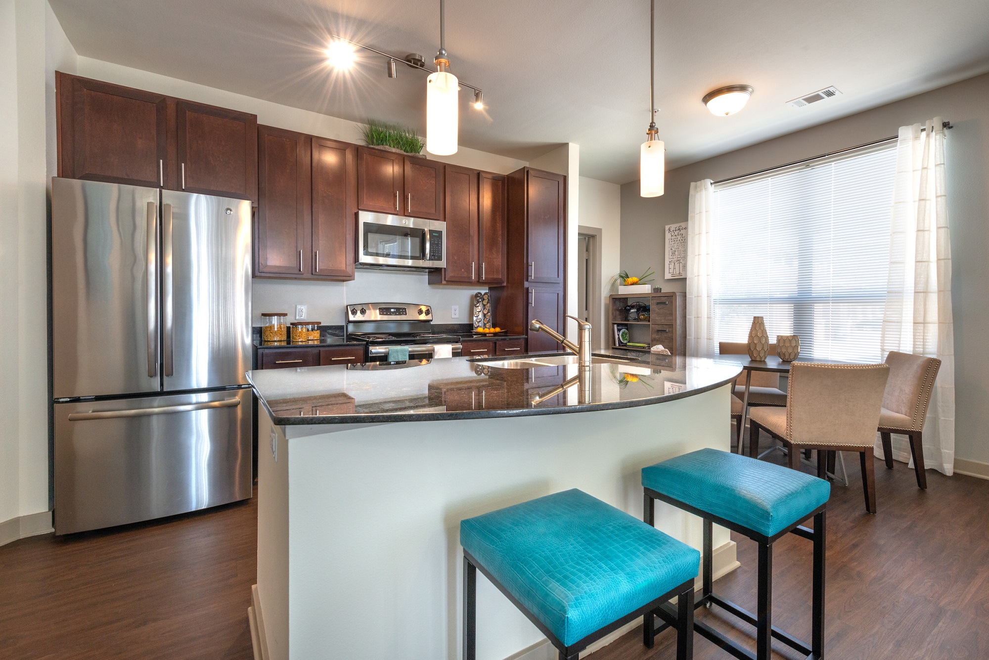 Kitchen with wood floors, designer lighting, kitchen island with bar seating, dining nook, granite counters and stainless steel appliances