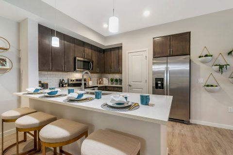 Model apartment kitchen with dark wood cabinets, subway tile backsplash, quartz countertops, stainless steel appliances, and barstool seating at counter