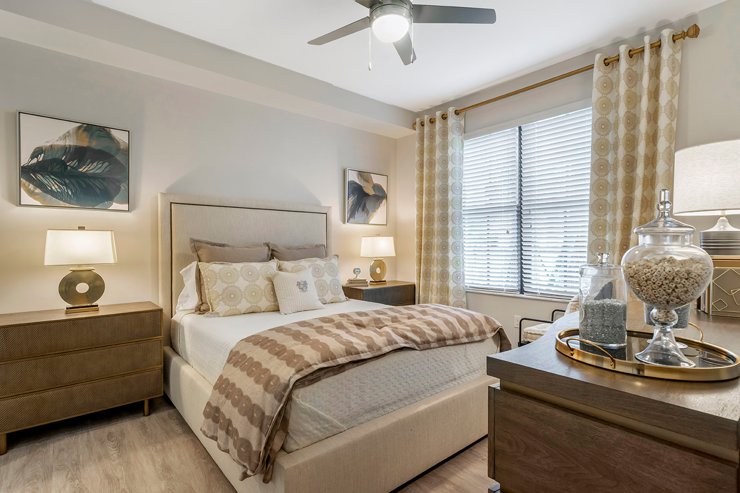 Model apartment bedroom with queen bed, end tables, large window, and ceiling fan