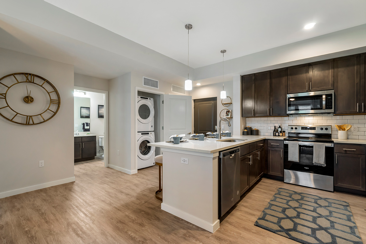 Model apartment kitchen with dark wood cabinets, wood-style plank flooring, and stainless steel appliances with view of washer and dryer machines