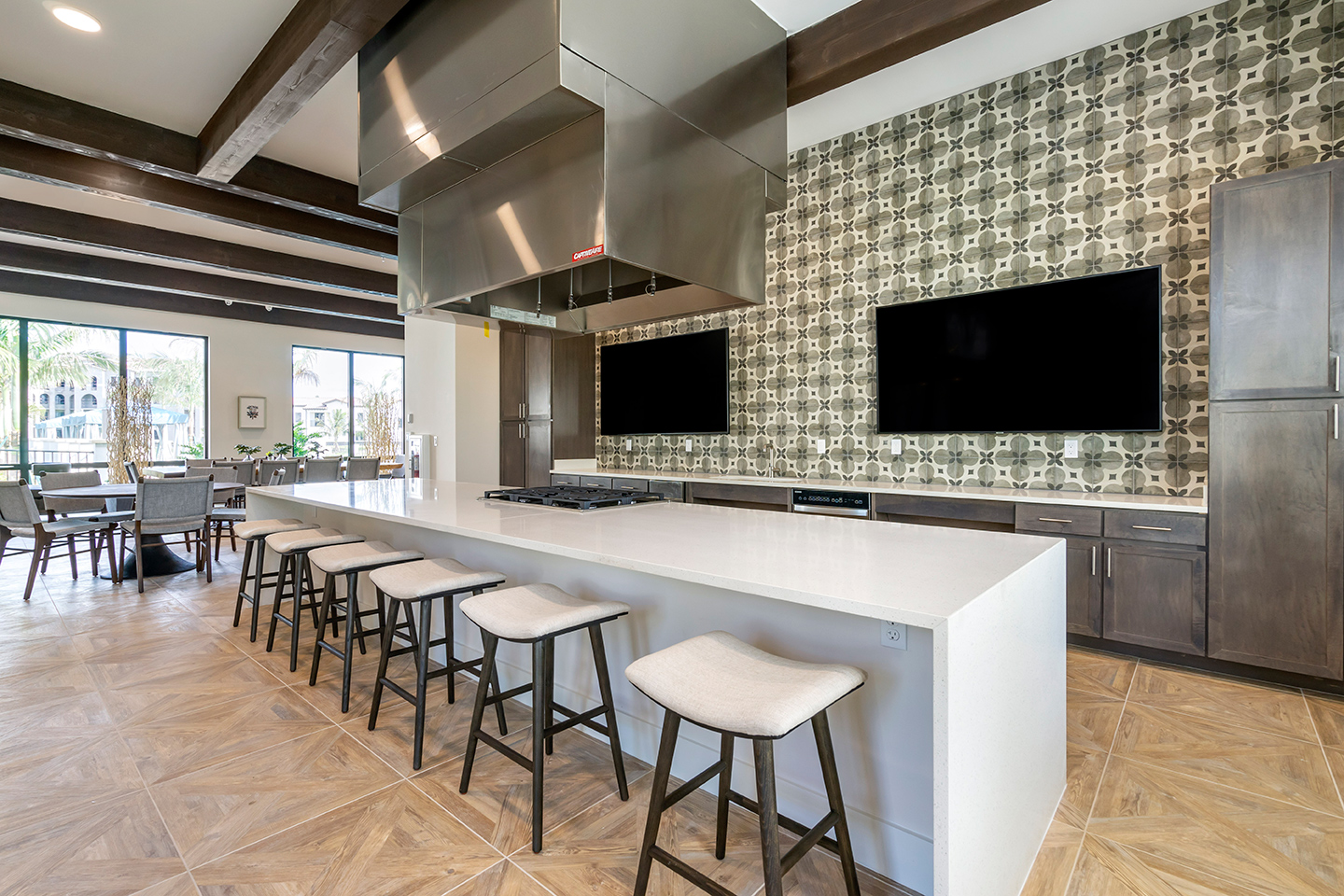 Demonstration kitchen with large TV screens, gas range, cabinets, and barstool seating