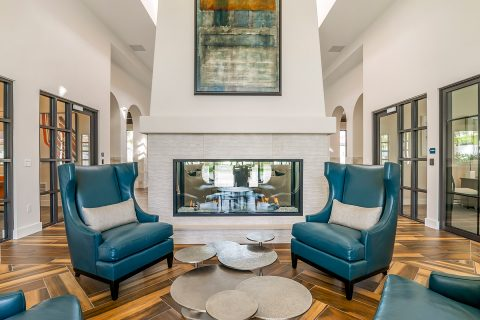 Community lobby with large leather armchairs, sculptural coffee table, and fireplace