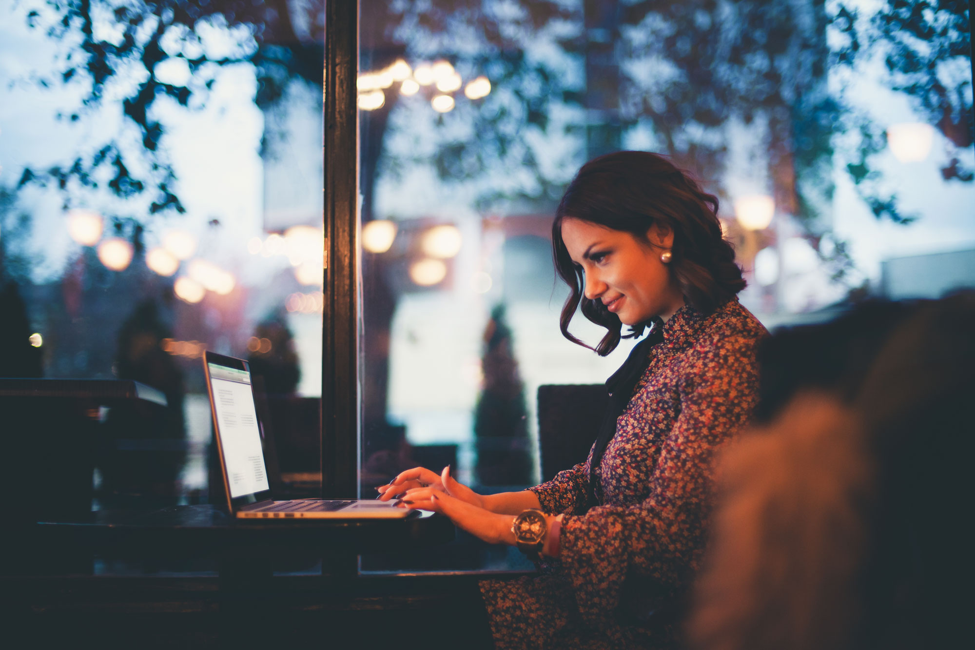 middle age woman sitting in cafe on laptop computer