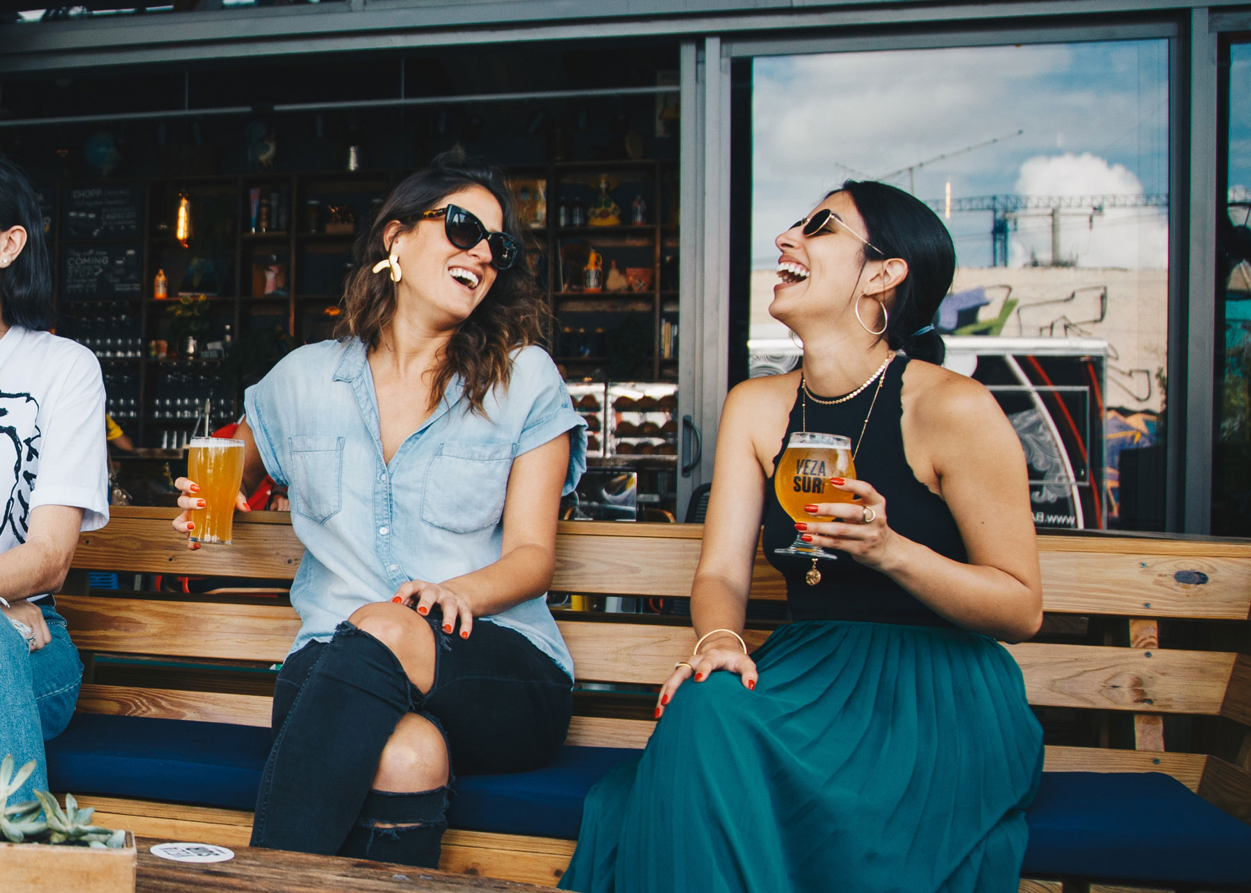 Women friends laughing, drinking craft beer and relaxing at outdoor pub
