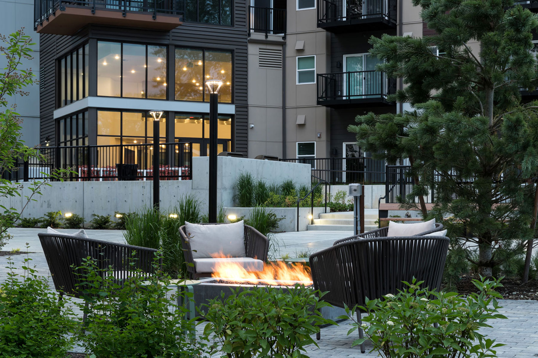 Dusk shot of the courtyard with fire pit, plush seating, green landscaping and apartment lobby in the background