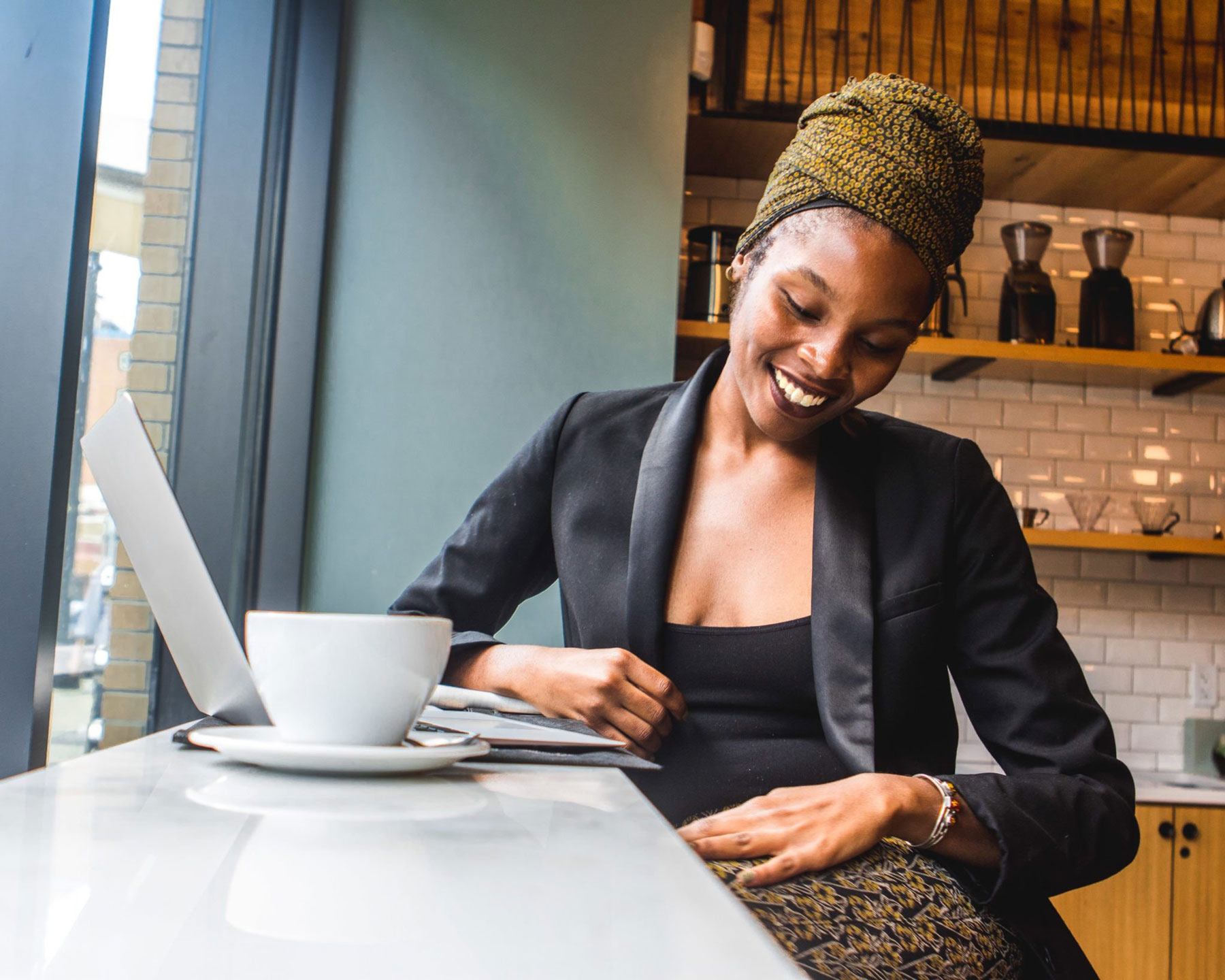 Middle age African American woman sitting with laptop and coffee at a cafe
