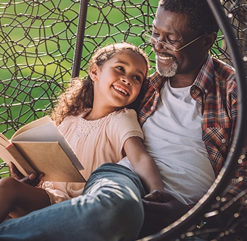 man and grandaughter sitting in a hanging chair reading a book in a park