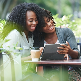 Young women sharing coffee and looking at a tablet.