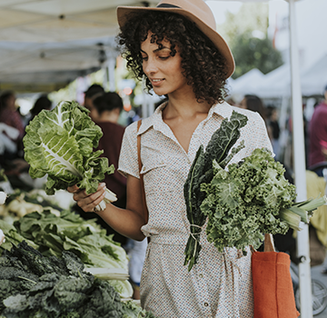 Young woman shopping for vegetables in a farmers market.