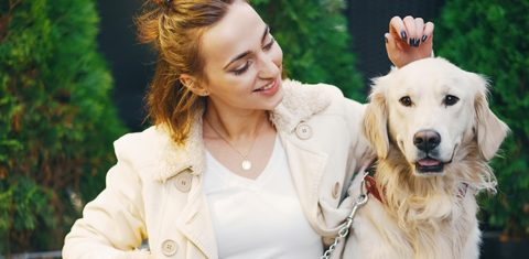 woman with jacket in a park with her dog