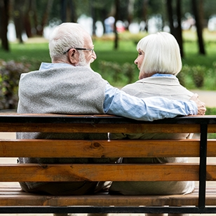 Older couple sitting on a park bench.